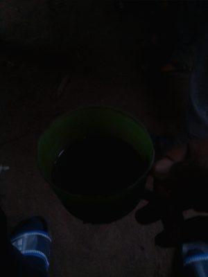 Du café sans sucre servie dans un gobelet en plastique.Les hommes du villages partageant du café dans la Véranda à Rugetsi. ©Hervé Mukulu
